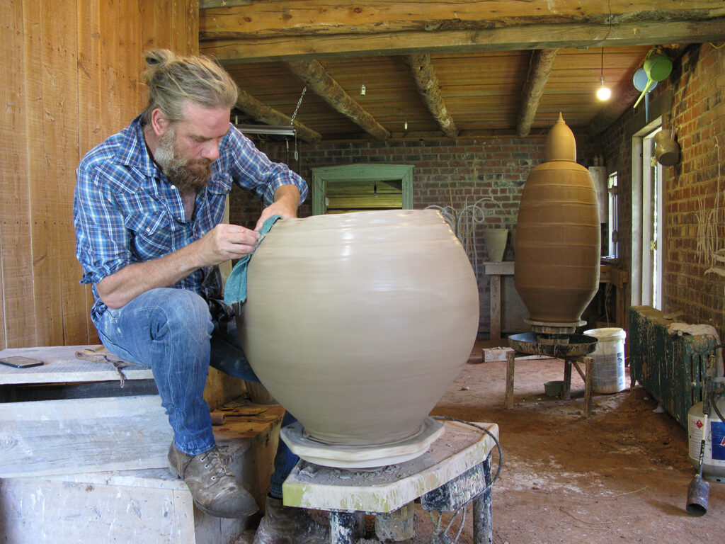 Artist Daniel Johnston sitting at a potter's wheel, working on a large pot